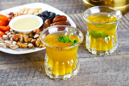 Oriental tea with mint, honey, nuts and dried fruits on wooden table background. Ramadan drink