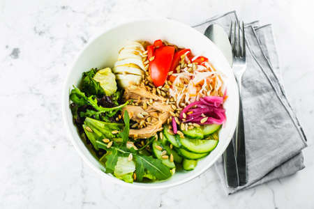 Tuna lunch bowl. Salad with green mix, vegetables, tuna and seeds. Healthy food concept. Top view