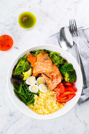Healthy meal, keto food concept. Fish salad bowl on marble table background. Salad with salmon, couscous, vegetables, quail eggs. Top view, copy space