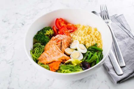 Healthy meal, keto food concept. Fish salad bowl on marble table background. Salad with salmon, couscous, vegetables, quail eggs. Close-up