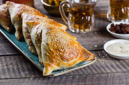 Eastern cuisine. Delicious samosas samsa with meat, glass of tea on wooden table background. Ramadan food