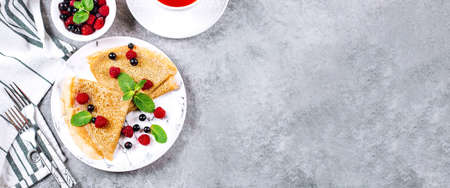 Delicious Crepes Breakfast on gray concrete table background. Orthodox holiday Maslenitsa. Pancakes with berry black currant, raspberry, jar of honey and mint. White cup of tea. Top view, copy space, banner for website