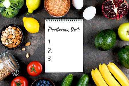 Flexitarian Diet Concept. Green vegetables, tomatoes, nuts, fruits, lentils, chickpeas, greens and empty notebook blank on grey concrete table. Flat lay, top view, copy space
