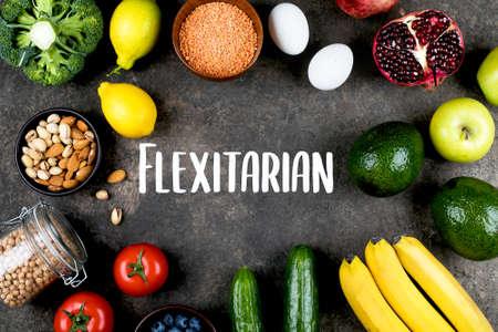 Flexitarian Diet Concept. Green vegetables, tomatoes, nuts, fruits, lentils, chickpeas, greens on dark slate table background. Flat lay, top view. Food frame with place for text, mockup concept