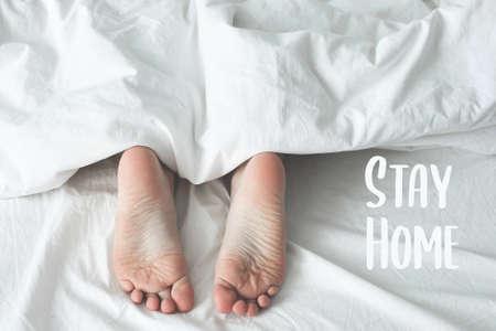 Child`s heels under blanket on bed Archivio Fotografico
