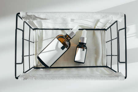 Bottle Mock-Up. Two cosmetics bottles in metal basket. Top view, copy space. Beauty concept