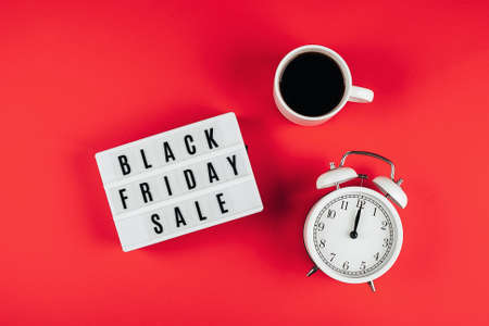 Black friday sale word on lightbox, cup of coffee, alarm on red background table. Flat lay, top view