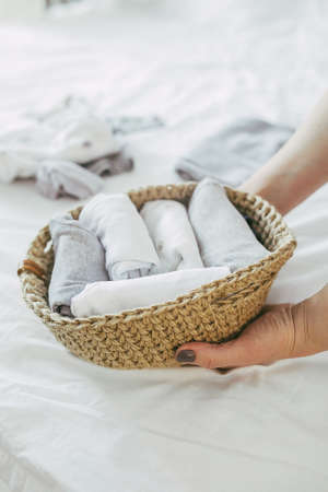 Woman folding clothes in jute basket in the konmari system. Concept of organizing minimalism clothes.