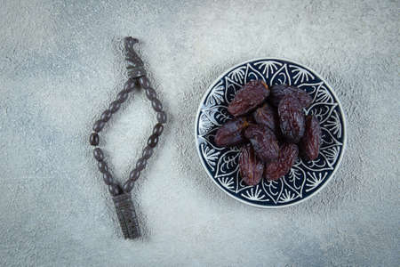 Ramadan kareem. Fresh Dates on plate and rosery beads on light concrete background. Top view.