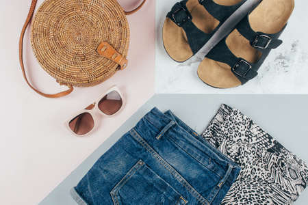 Flat lay with summer women's clothing and accessories. White t-shirt, blue denim shorts, fashionable organic rattan bag, sunglasses. Vacation, travel concept. Top view