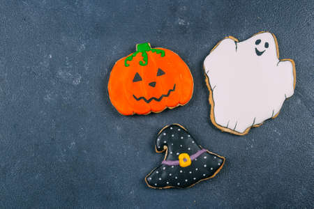 Morning Breakfast Halloween Fall Autumn Concept. Pumpkin gingerbread cookie and cup of black coffee on wooden rustic background. Top view