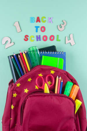 Red backpack with different colorful stationery on yellow background. Back to school concept. Top view, copy space Standard-Bild