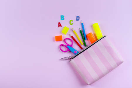 Back to school concept. School supplies in pencil case. Pink background with copy space. Flat lay, view from above. Standard-Bild