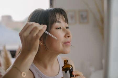 Concept of morning routine, still life, wellness. Young asian woman doing facial massage with quartz pink gouache scrap at home Standard-Bild