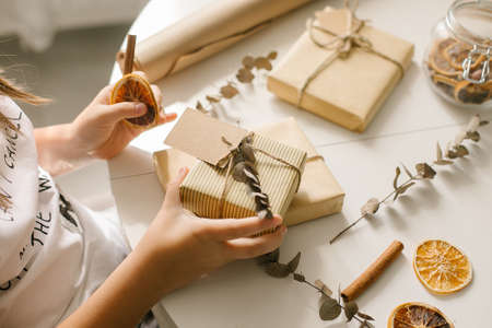 Holiday preparation and gift wrapping with craft paper on white table. Gift wrapped in brown paper and tied with rough twine and label for text. Top view