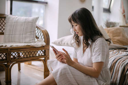 Side view of woman sitting on floor at home, using mobile application on cellphone or chatting, reading texts, close-up Standard-Bild