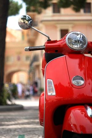 vespa piaggio: Red scooter d'epoca parcheggiate nelle strade di Monaco