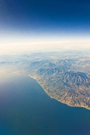 View from plane on the clounds and earth under photo