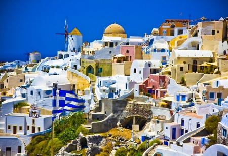 Amazing view on Oia city with waving Greek flag