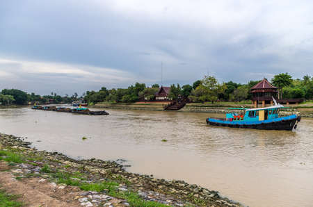 tug boat: Ayutthaya, Thailand - July 07, 2013   Tug boat towing barges filled with ore on the Chao Phraya river in Ayutthaya, Thailand  Editorial
