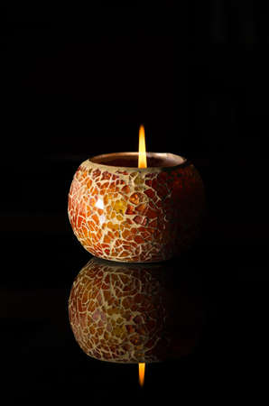 ignited: A lit candle lamp isolated against black background