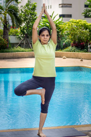 arms lifted up: A woman practicing a yoga pose standing on one leg and arms lifted up