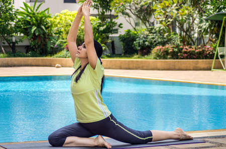 ancient yoga: A woman practicing a yoga pose next to a swimming pool Stock Photo