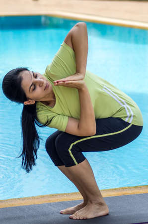 knees bent: A woman practicing a yoga pose with knees bent ann torso twisted Stock Photo