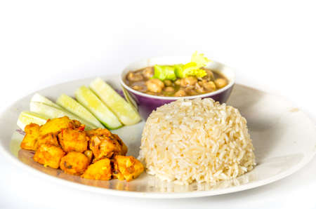 Indian vegetarian meal of brwon rice with potato and chickpea curry photo