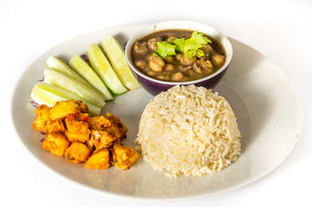 Indian vegetarian meal of brwon rice with masala potato and chickpea curry photo