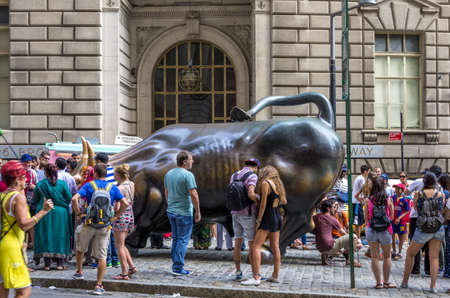 New York, NY - August 9th, 2014 : Tourists admiring the Wall Street Bull. The Charging Bull, which is sometimes referred to as the Wall Street Bull or the Bowling Green Bull, is a 3,200-kilogram bronze sculpture by Arturo Di Modica that stands in Bowling