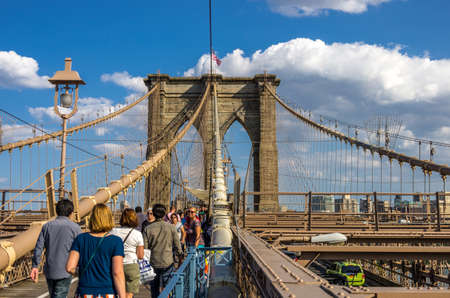 boroughs: New York, NY - August 9th, 2014 : Tourists on the  Brooklyn Bridge which is one of the oldest suspension bridges in New York, United States. It was completed in 1883, and connects the boroughs of Manhattan and Brooklyn by spanning the East River in New Yo