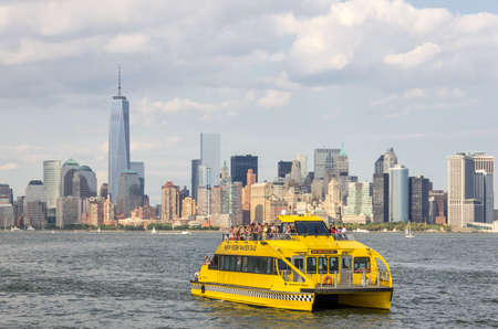 New York, NY - September 10, 2014 : The New York Water Taxi sailing on the Hudson river with the view of Manhattan skyline in New York, USA