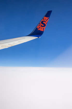 New York, NY - August 11, 2014 : The logo of Sun Country airlines on the wing of the plane in New York, USA. Captured in mid flight against a carpet of clouds and blue sky.