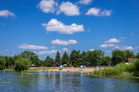 Eden Prairie, MN - August 12, 2014 - People sunbathing and relaxing at Round lake in Eden Prairie, MN, USA. It is named round lake as it is absolutely round in shape.