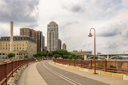 mn: minneapolis, Minnesota - August 21, 2014: The Stone Arch bridge across the Mississippi river at the famous Mill Ruins Park in Minneapolis, MN, USA