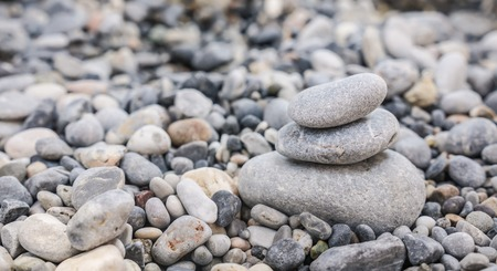 Small tower made of pebbles on a rocky beach