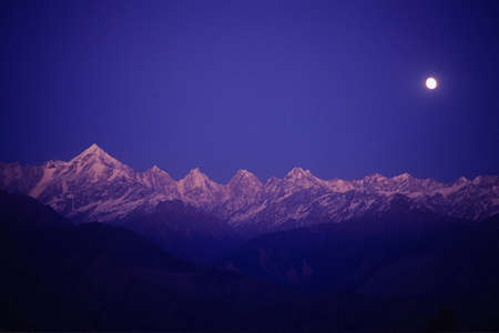 Panchchuli Peaks, Munsyari, Uttarakhand, India: 13 December, 2006: Pink color Panchchuli Peaks and full moon in the sky view from Munsyari at Uttarakhand, India.The Panchchuli peaks are a group of five snow-capped Himalayan peaks lying at the end of the e