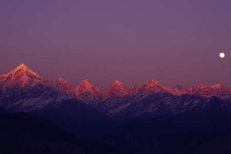 Panchchuli Peaks, Munsyari, Uttarakhand, India: 28July, 2005: Pink color Panchchuli Peaks and full moon in the sky view from Munsyari at Uttarakhand, India.The Panchchuli peaks are a group of five snow-capped Himalayan peaks lying at the end of the easter