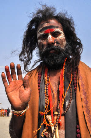 Allahabad, Uttar Pradesh, India- 15 January, 2013: An Aghori Sadhu with long hairs, ash and tilak on face wearing human bones and  rudraksha bead at Mahakumbh mela, Allahabad, Uttar Pradesh, India.The Aghori are known to engage in post-mortem rituals.  Th