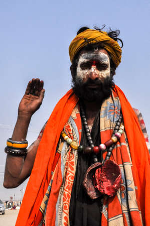 Allahabad, Uttar Pradesh, India- 15 January, 2013: An Aghori Sadhu with long hairs, ash and red color holy mark on face wearing human bones and  rudraksha bead at Mahakumbh mela, Allahabad, Uttar Pradesh, India.The Aghori are known to engage in post-morte Editorial