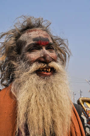 Allahabad, Uttar Pradesh, India- 15 January, 2013: Smile of An Aghori Sadhu with long hairs, ash and holy mark on face wearing human bones and  rudraksha bead at Mahakumbh mela, Allahabad, Uttar Pradesh, India.The Aghori are known to engage in post-mortem Editorial