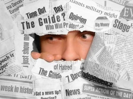 desconfianza: Hombre mirando scepticly a través de los periódicos