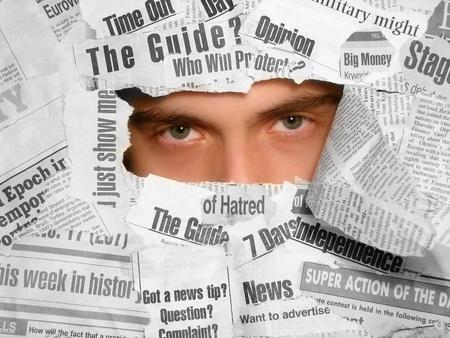 desconfianza: Hombre mirando tiredly a trav�s del collage de peri�dicos Foto de archivo
