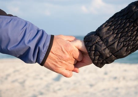 touching hands: Mature couple holding hands on a beach Stock Photo