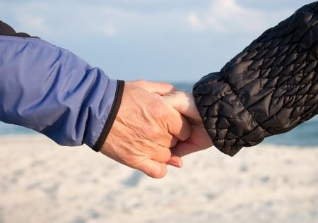 Mature couple holding hands on a beach Foto de archivo