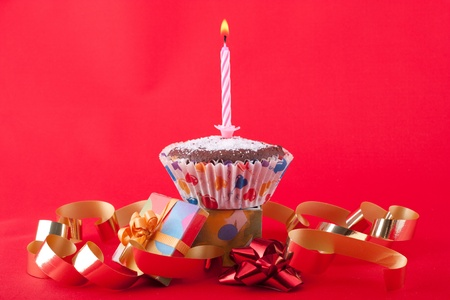 Birthday candle on a cupcake with present and decoration photo