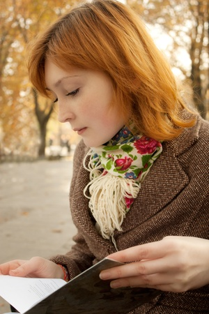 Beautiful redhead girl reading a book in an autumn park photo