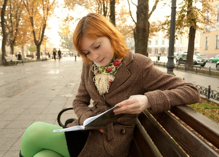 Beautiful redhead girl reading a book on a bench in an autumn park photo