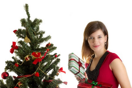 Beautiful woman with presents near Christmas tree photo